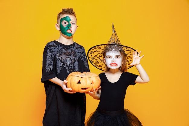 Kinderen in halloween-kostuums spelen met pompoen