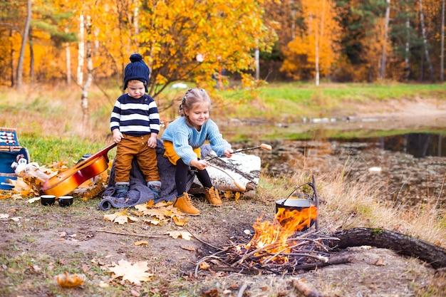 Kinderen in het herfstbos op een picknickgrill worstjes en gitaar spelen