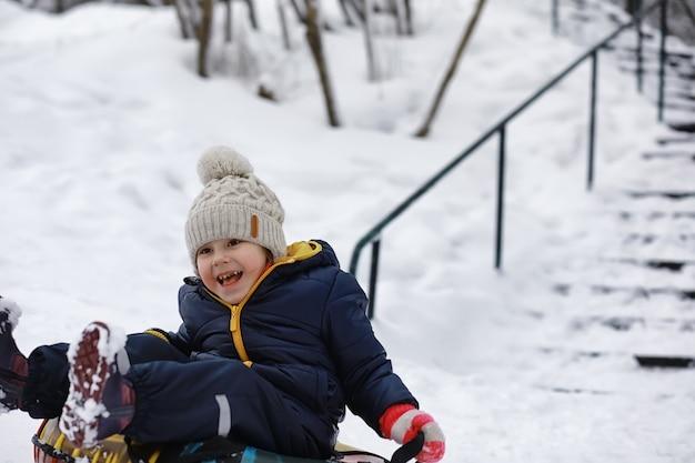 Kinderen in het park in de winter. kinderen spelen met sneeuw op de speelplaats. ze boetseren sneeuwmannen en glijden van de heuvels.