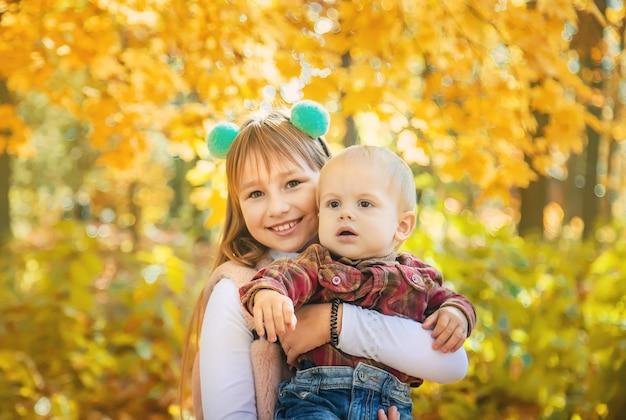 Kinderen in het park met herfstbladeren.
