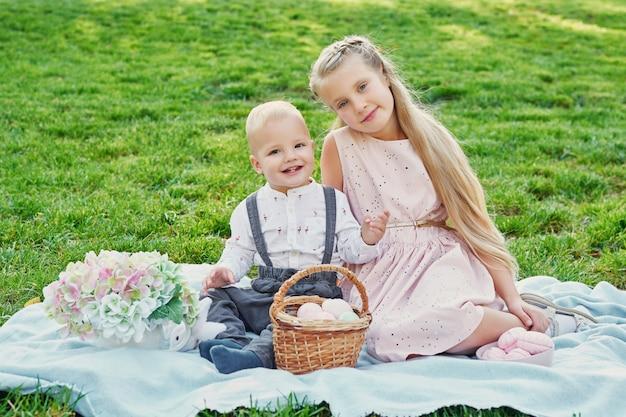 Kinderen in het park op pasen-picknick met eieren en konijn