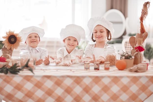 Kinderen in het uniform van de chef koken een dessert dat bij de keukentafel staat. het concept van een hobby