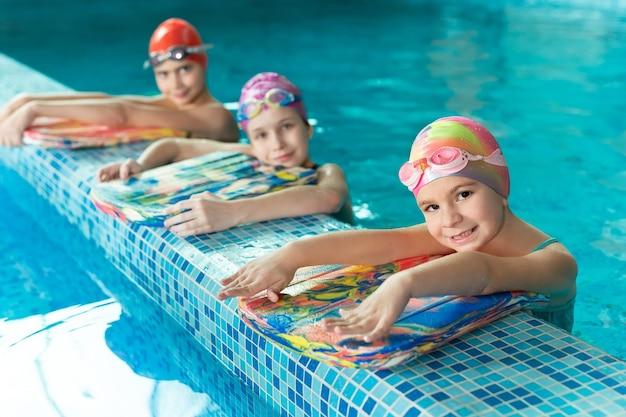 Kinderen in het zwembad met zwemplanken tijdens de training.