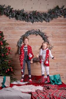Kinderen in hetzelfde gezin zien eruit als een zachte, warme pyjama die thuis speelt op kerstavond onder een versierde kerstboom. gelukkig kind springen op het bed. nieuwjaars vakantie.