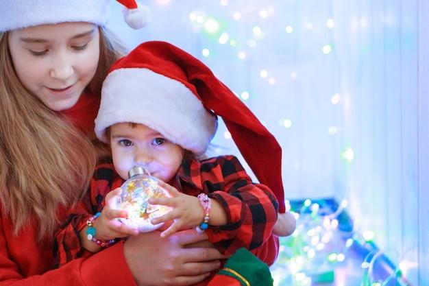 Kinderen in kerstkostuums met een kerstboomspeelgoed. concept van nieuwjaar, maskerade, feestdagen, decoraties