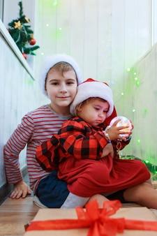 Kinderen in kerstkostuums met een kerstboomspeelgoed.