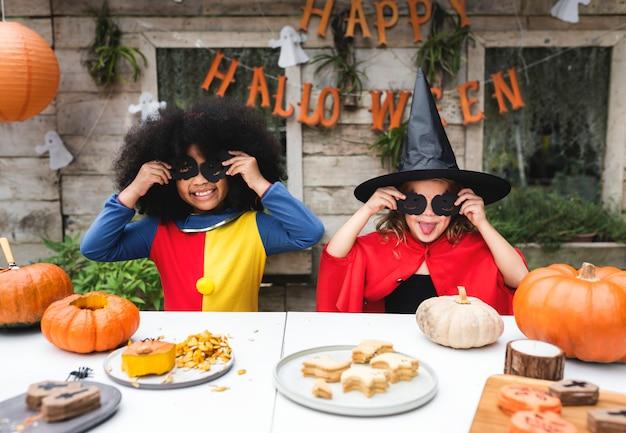 Kinderen in kostuum die van het halloween-seizoen genieten