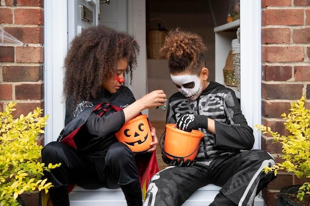 Kinderen in kostuums die hun snoepjes eten