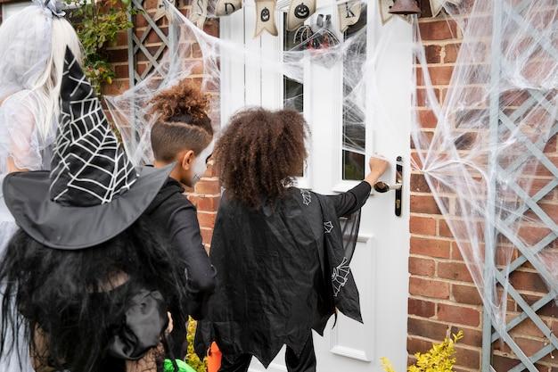 Kinderen in kostuums trick or treat bij iemand thuis
