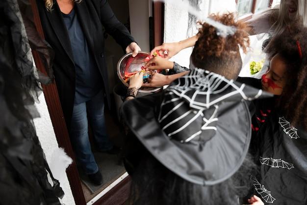 Kinderen in kostuums trick or treat op halloween