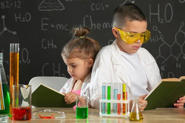 Kinderen in laboratorium met boek studeren