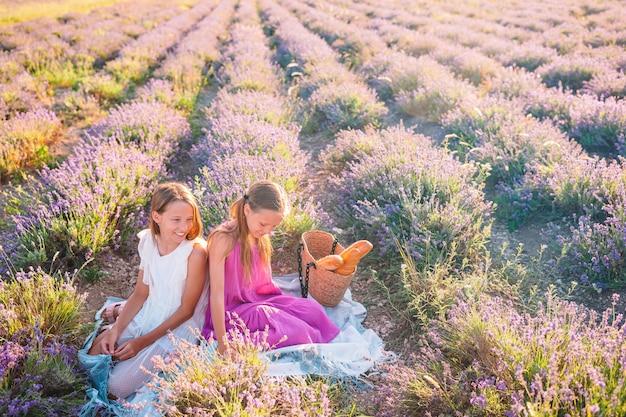 Kinderen in lavendel bloemen veld bij zonsondergang in witte jurk en hoed