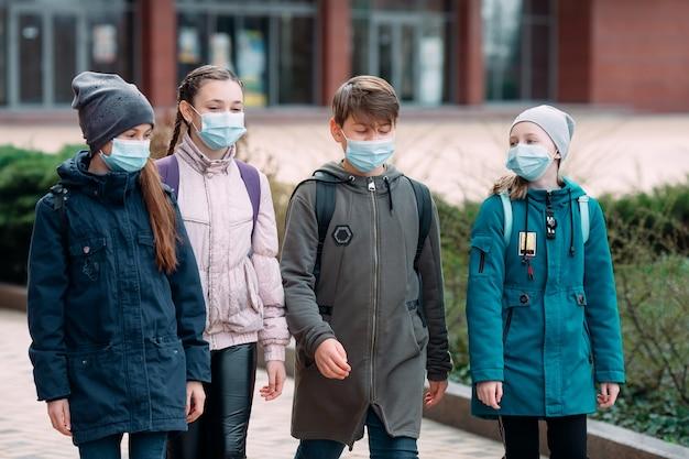 Kinderen in medische maskers verlaten de school.