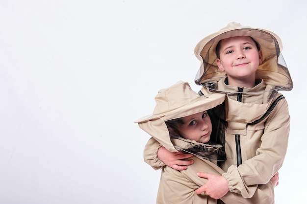 Kinderen in pakken van de imker poseren in studio witte achtergrond.
