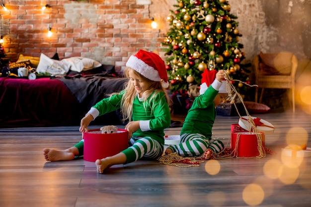 Kinderen in pyjama's en kerstmutsen pakken kerstcadeautjes uit Premium Foto