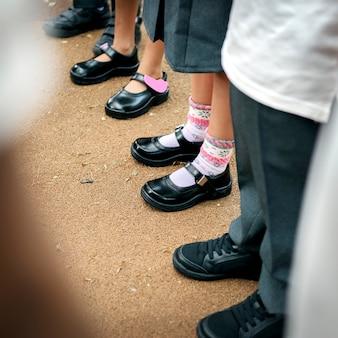 Kinderen in schooluniform in de rij staan