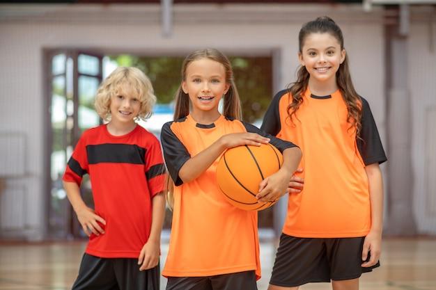 Kinderen in sportkleding staan met een bal en glimlachen gelukkig