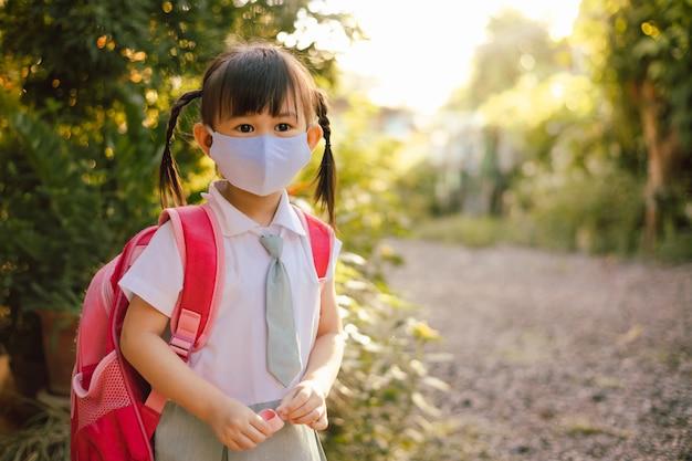 Kinderen in studentenuniform dragen gezichtsmasker als nieuwe normale gewoonten voor viruspreventie.
