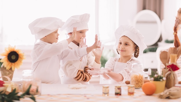 Kinderen in uniform van de chef geven elkaar een high five. het concept van een hobby