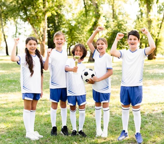 Kinderen in voetbaluitrusting die enthousiast zijn over een nieuwe wedstrijd