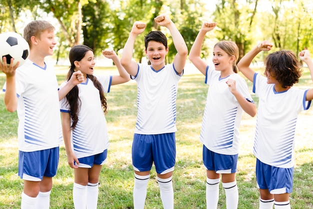 Kinderen in voetbaluitrusting die na een wedstrijd zegevierend kijken