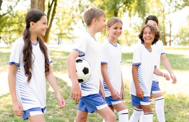 Kinderen in voetbaluitrusting die zich klaarmaken voor een wedstrijd