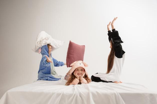 Kinderen in zachte warme pyjama's die thuis spelen, vechtend met kussens. kleine meisjes die plezier hebben, feesten, samen lachen, zien er stijlvol en gelukkig uit. concept van kindertijd, vrijetijdsbesteding, geluk.