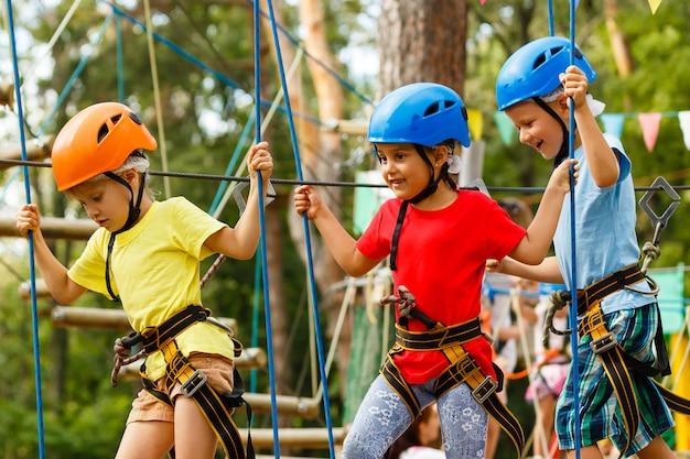 Kinderen, jongen en een meisje in het touwpark passeren obstakels. broer en zus beklimmen de touwweg