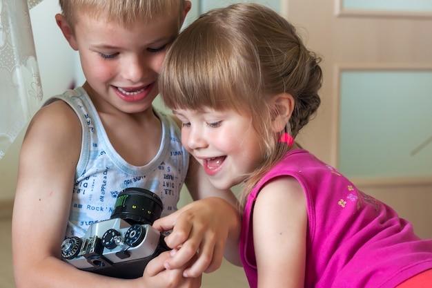 Kinderen jongen en meisje broer en zus spelen met camera's.