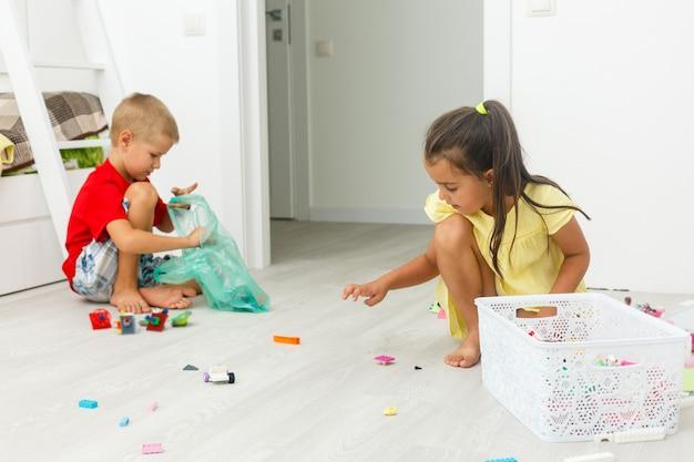Kinderen jongen en meisje broers en zussen spelen thuis met educatieve speelgoed blokken