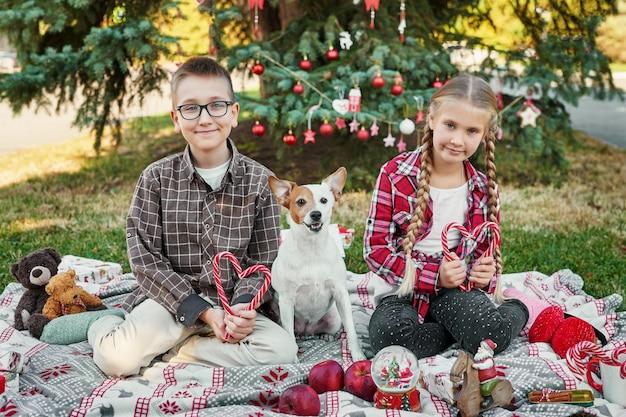 Kinderen jongen en meisje met een hond jack russell terrier in de buurt van een kerstboom met geschenken,