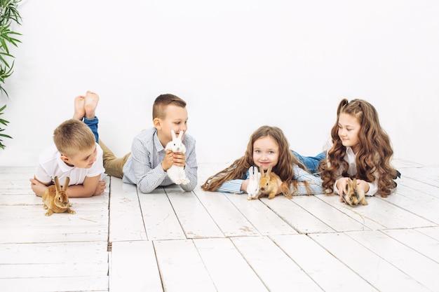 Kinderen jongens en meisjes blij mooie pluizige kleine konijntjes op de witte achtergrond van de muur