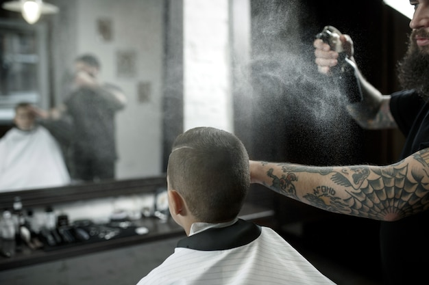 Kinderen kapper kleine jongen snijden tegen een donker