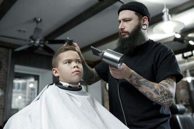 Kinderen kapper kleine jongen snijden tegen een donkere achtergrond.