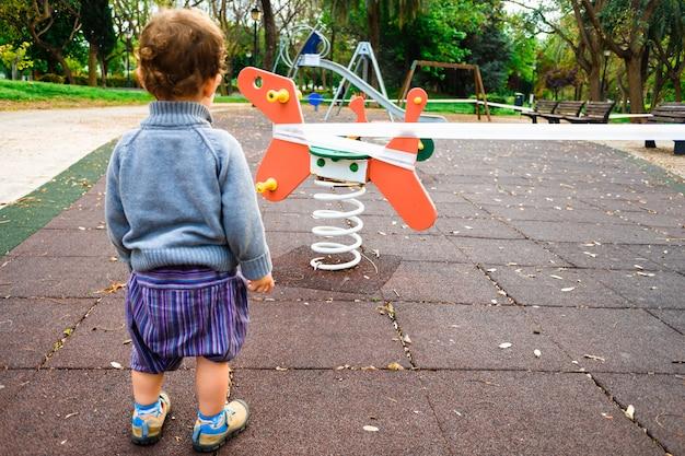 Kinderen kijken naar een gesloten speeltuin in een stad om de verspreiding van virussen te voorkomen.