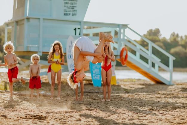 Kinderen kijken naar een jongen die op het strand springt