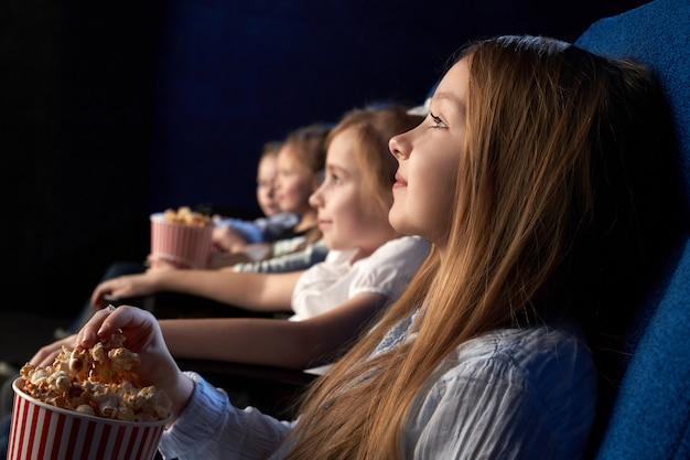 Kinderen kijken naar film in bioscoop.