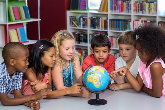 Kinderen kijken naar globe op tafel