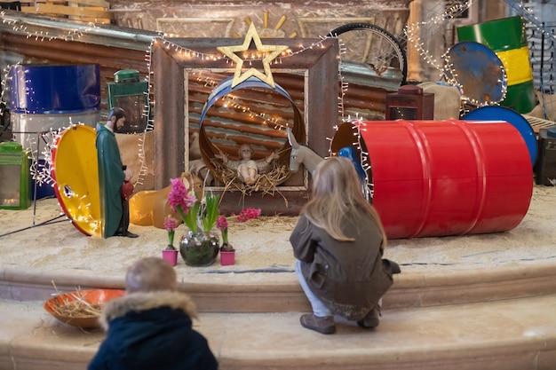 Kinderen kijken naar kerstcrèche met jozef maria en kleine jezus in een wieg