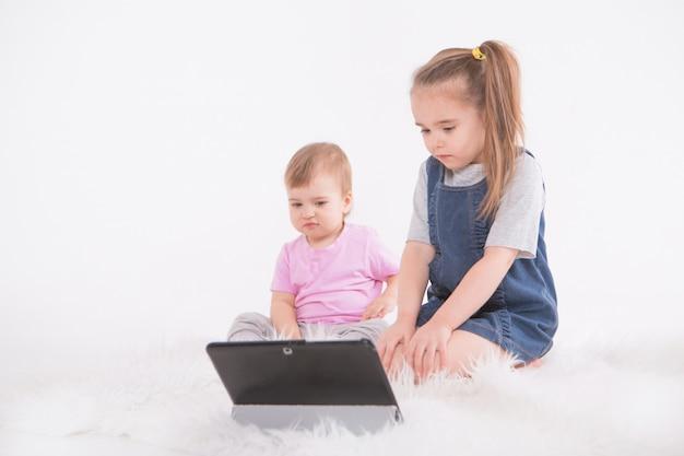 Kinderen kijken naar tekenfilms op de tablet. thuisonderwijs voor meisjes tijdens quarantaine