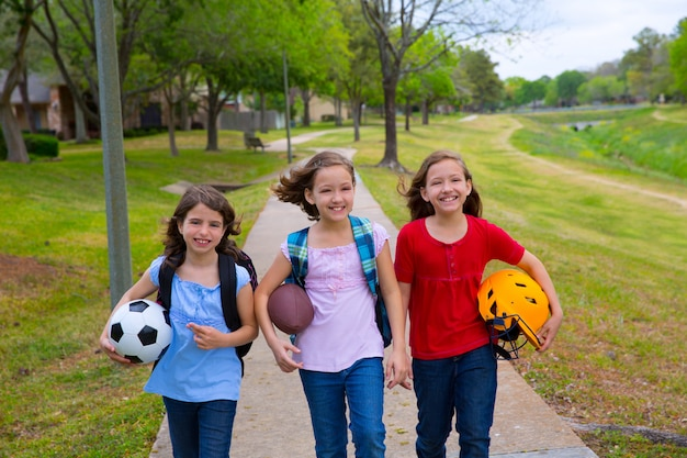 Kinderen kind meisjes lopen naar schoele met sport ballen