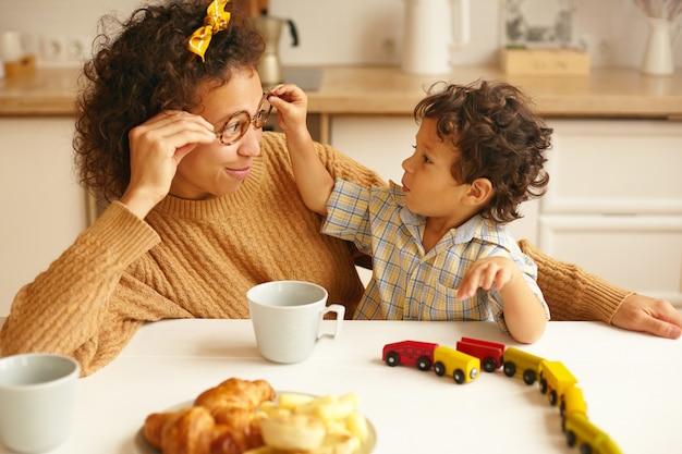 Kinderen, kinderen, gelukkige jeugd, familiebanden en ouderschap concept. foto van aantrekkelijke jonge spaanse vrouw met koffie aan de keukentafel en glimlachen terwijl zoontje haar bril opstijgt
