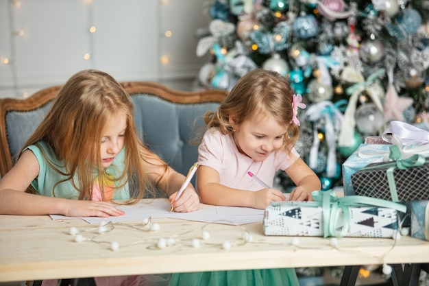Kinderen, kleine meisjes, zussen met geschenken, mooi in het kerstinterieur, schrijven een brief aan de kerstman