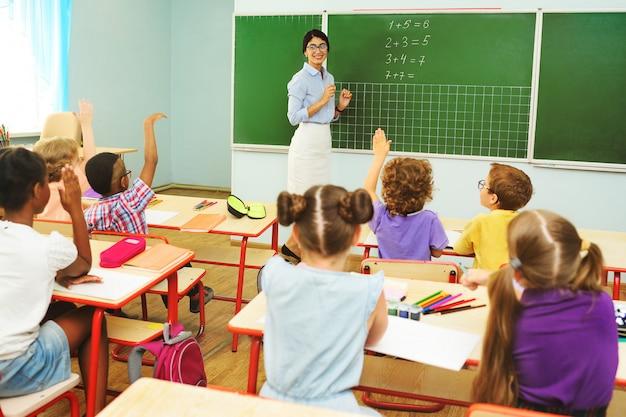 Kinderen kleuters steken hun handen op om de vraag van de leraar te beantwoorden, klaslokaal op de basisschool.
