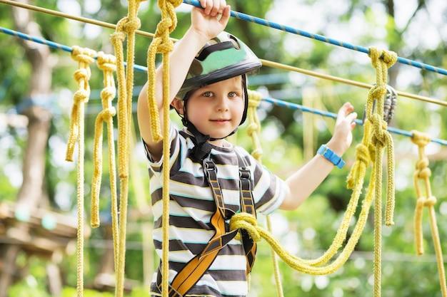 Kinderen klimmen in avonturenpark. jongen geniet van klimmen in het touwenparcoursavontuur. kind klimmen hogedraadpark