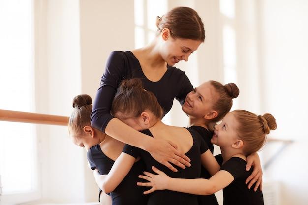 Kinderen knuffelen balletleraar