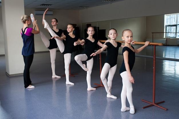 Kinderen krijgen ballethoudingen aangeleerd in choreografie.