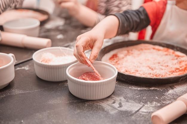Kinderen leggen de ingrediënten neer op basis van pizza
