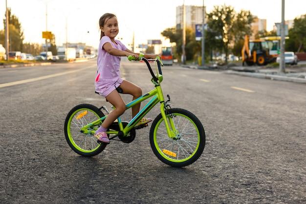 Kinderen leren autorijden op een oprit buiten. meisjes die fietsen berijden op asfaltweg in de stad die helmen dragen als beschermende uitrusting.