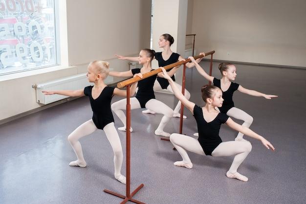 Kinderen leren balletposities in choreografie.